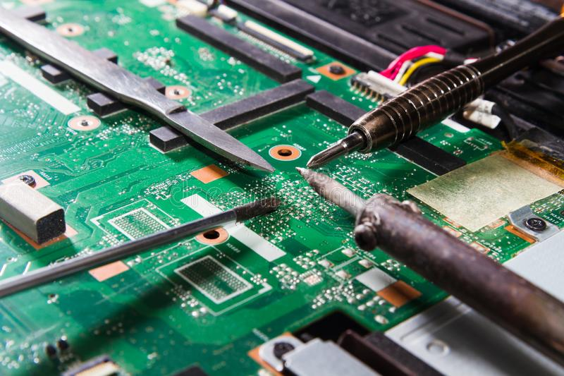 Printed circuit Board with tools green screwdriver, soldering iron, knife, close up royalty free stock images