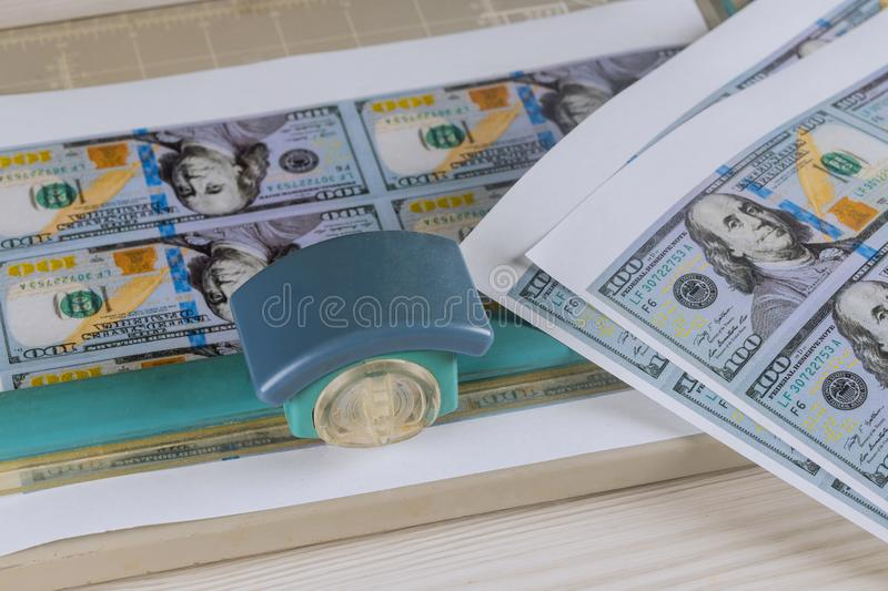 Printed fake money currency counterfeiting cutting a fake dollar cutter. Printed fake money currency counterfeiting cutting a fake US dollar cutter, crime stock image