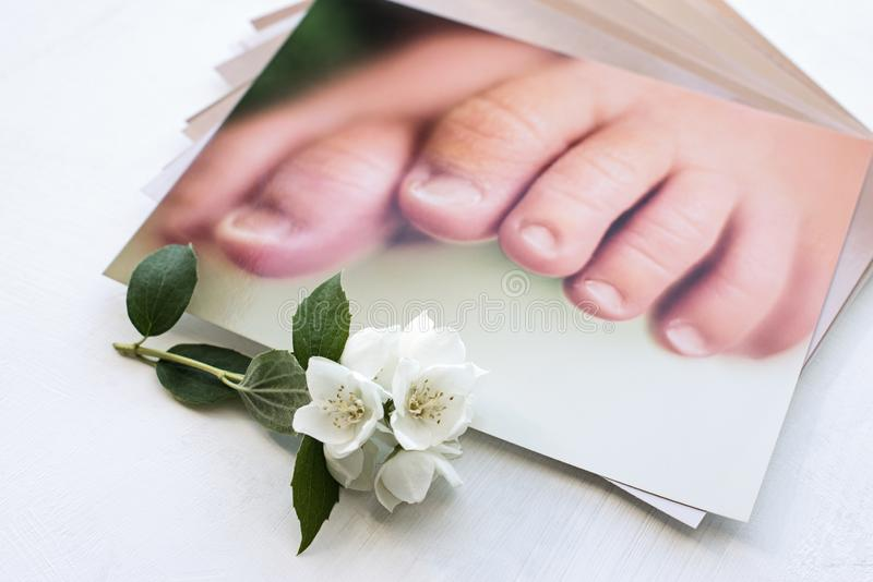 Printed photos and jasmine flower. memory of parents about childhood. Legs of a newborn baby royalty free stock photos