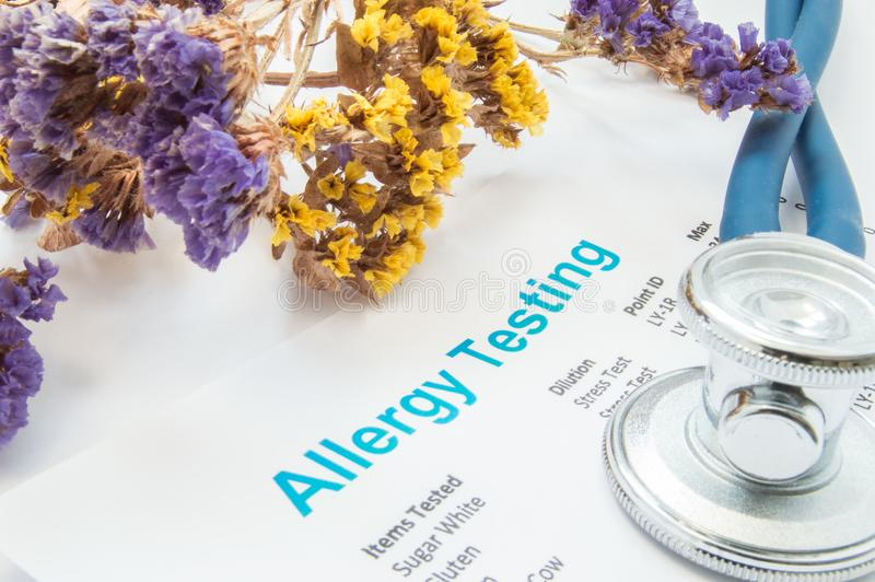 Printed result of allergy test blood or skin lies next to flowers with falling pollen and stethoscope. Concept photo for analysi royalty free stock images