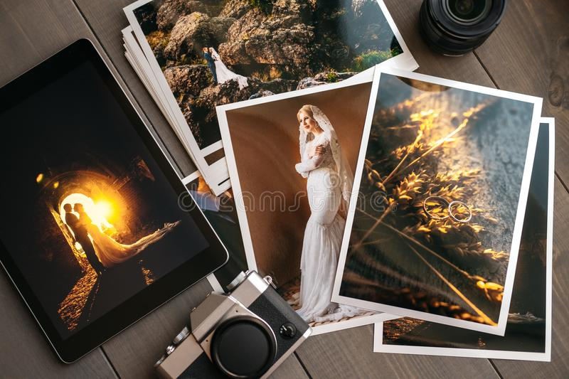 Printed wedding photos with the bride and groom, a vintage black camera and a black tablet with a picture of a wedding. Couple, on wooden background stock image