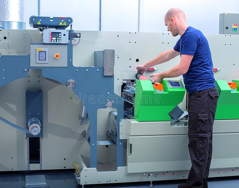 Printer operator next to the printing machine, holding printing cylinder with polymer relief plate stuck on it. stock photography
