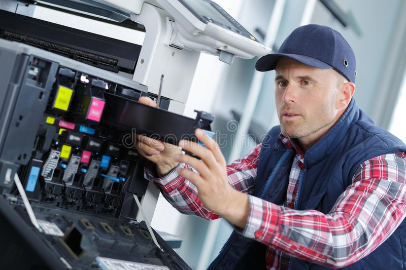 Printer technician removing cartridge container royalty free stock images
