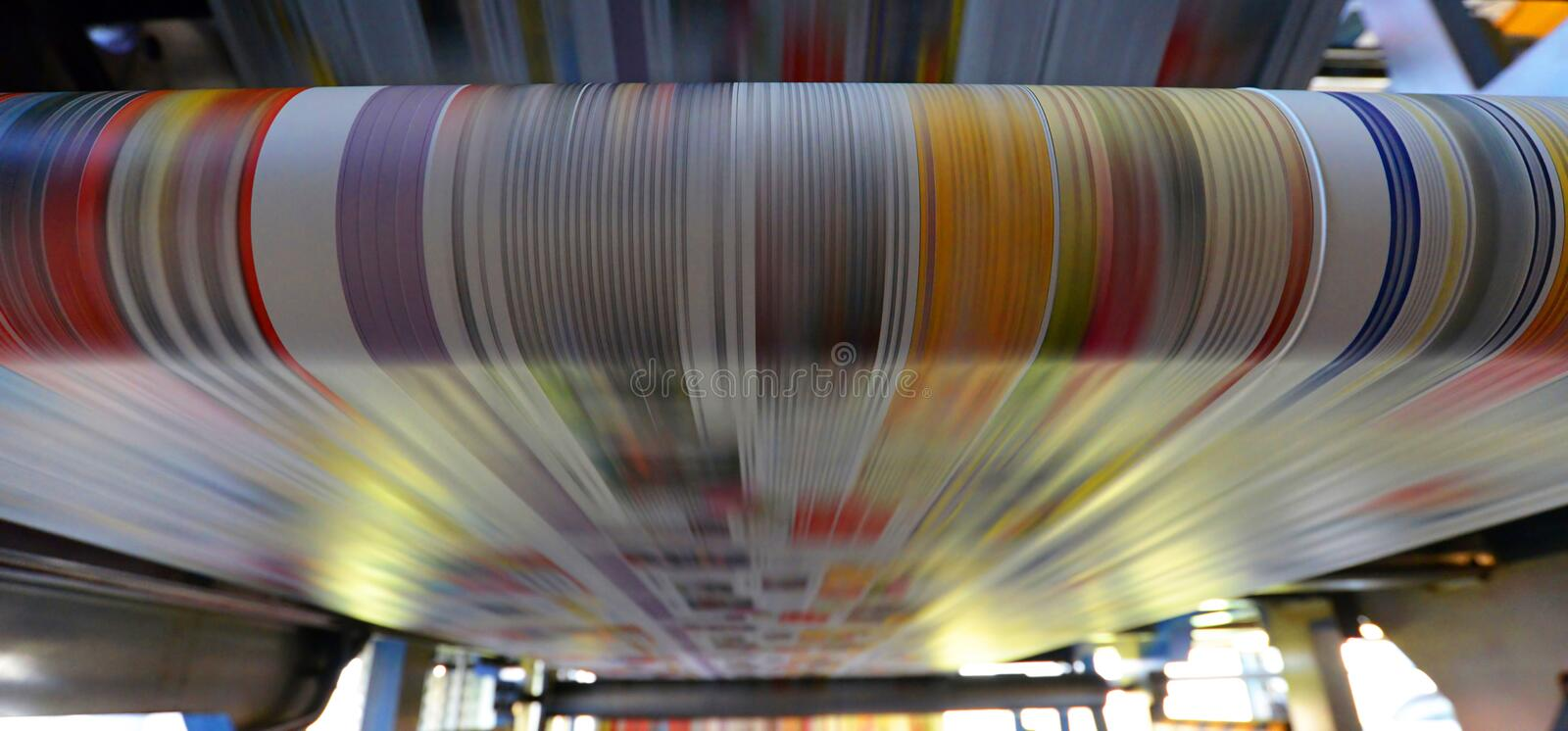 Printing of coloured newspapers with an offset printing machine. At a printing press stock images