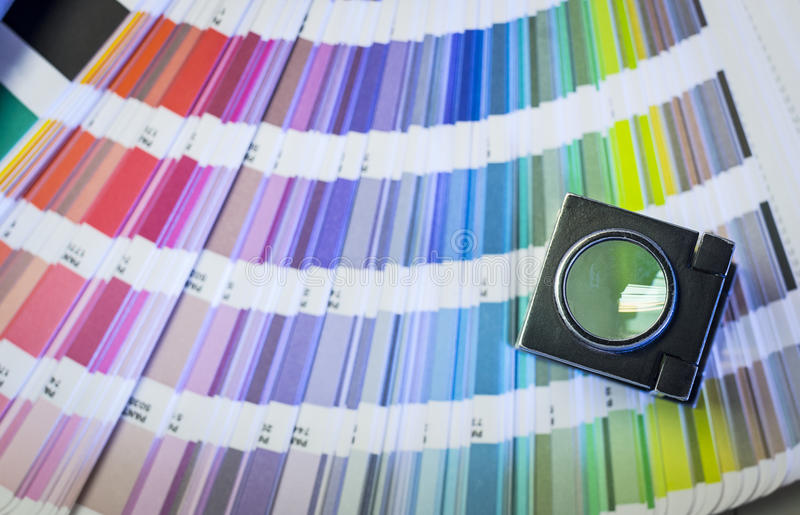 Printing process with magnifying glass and color swatches. Color management in printing process with magnifying glass and color swatches royalty free stock photos
