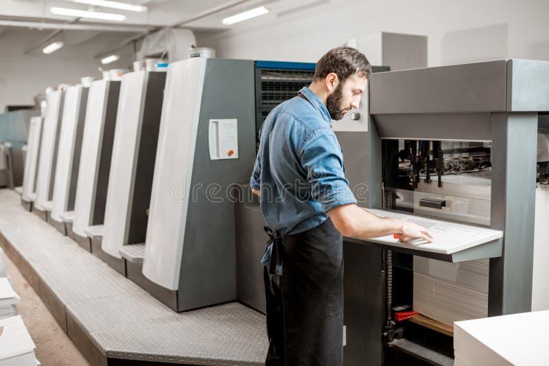 Printingoperatör som arbetar på tillverkningen arkivfoton