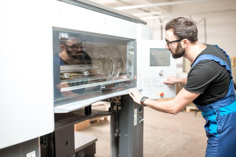 Printingoperatör som arbetar på tillverkningen arkivbild