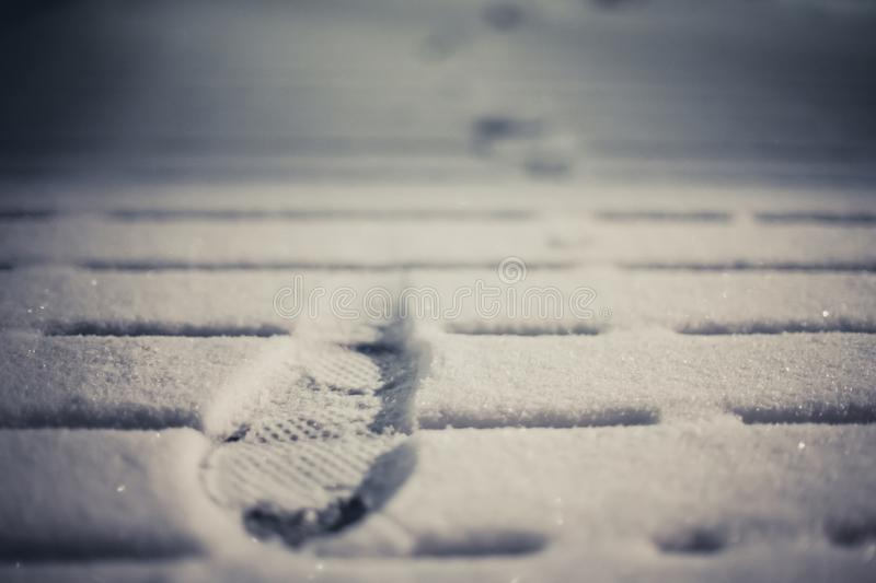 Prints in the snow from boots on deck stock photo