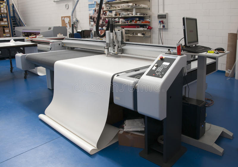 Printshop with cutting plotter. Cutting plotter (sometimes known as a vinyl sign cutter) is used by professional poster and billboard sign-making businesses to stock images