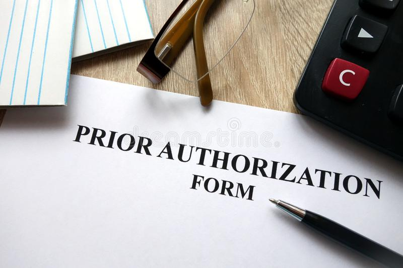 Prior authorization form. With pen, calculator and glasses on desk stock photo