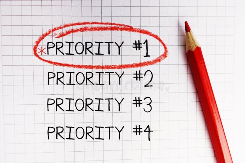Prioridade número um identificado por meio de círculo vermelho no caderno da matemática imagens de stock
