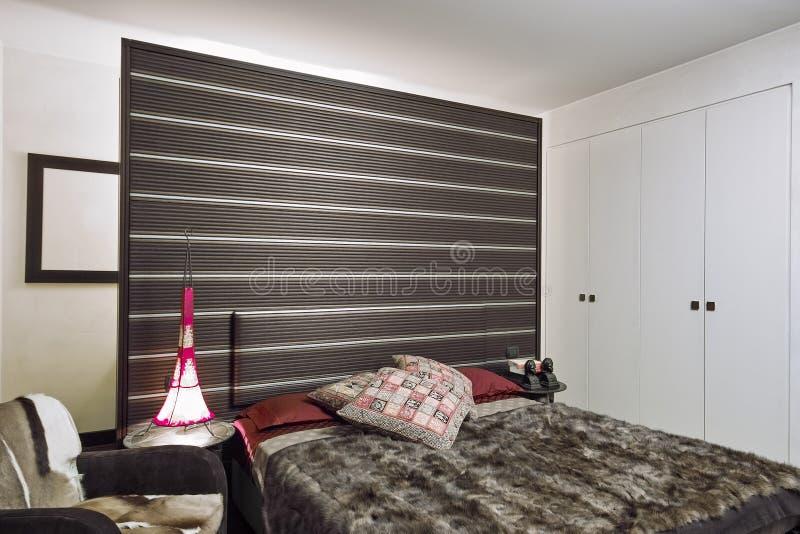 Priorità alta di un letto moderno con i cuscini immagini stock libere da diritti