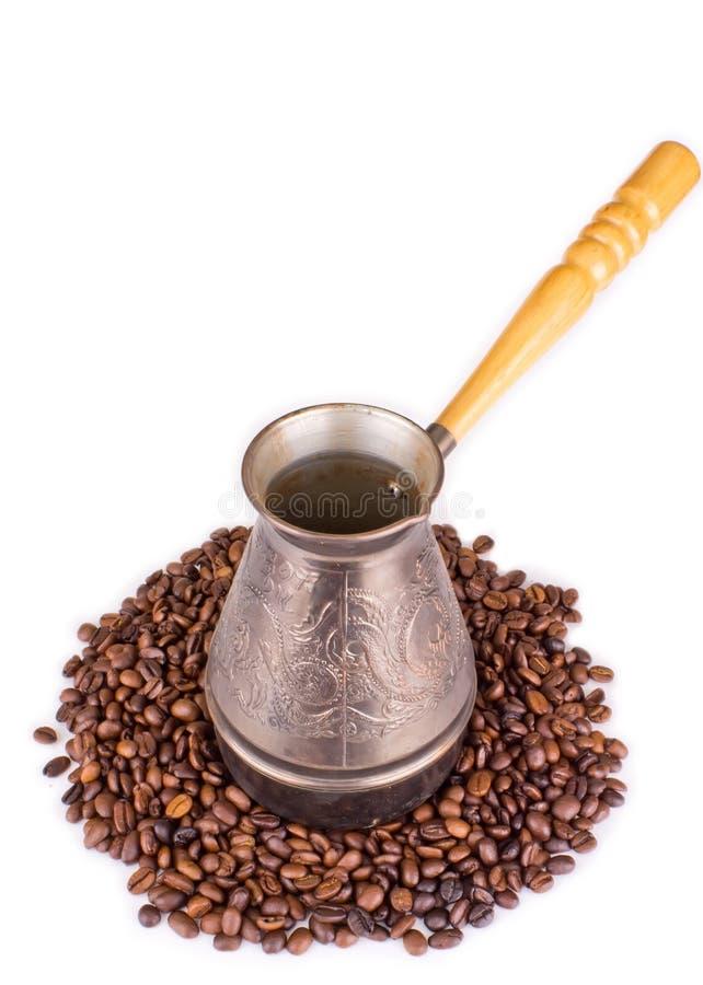 Priorità bassa con i chicchi di caffè e del cezve fotografia stock