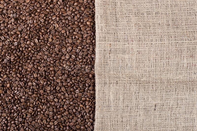 Priorità bassa del caffè con i fagioli e una tela di canapa immagini stock libere da diritti