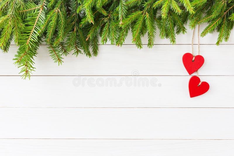 Priorità bassa di natale Albero di abete di Natale, decorazione rossa dei cuori su fondo di legno bianco con lo spazio della copi fotografia stock libera da diritti