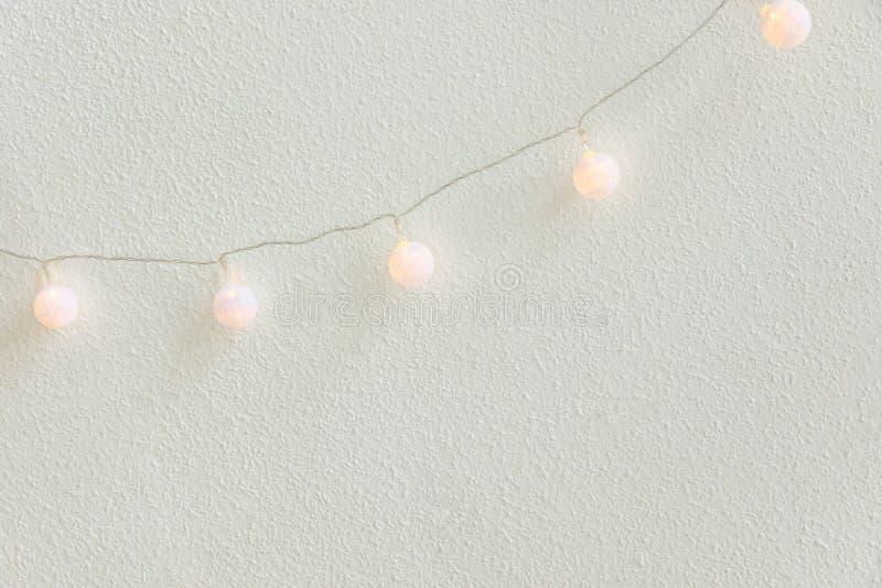 Priorità bassa di nuovo anno di natale Diagonale che appende le palle di cotone dorate pastelli Garland White Wall Background Sti fotografia stock