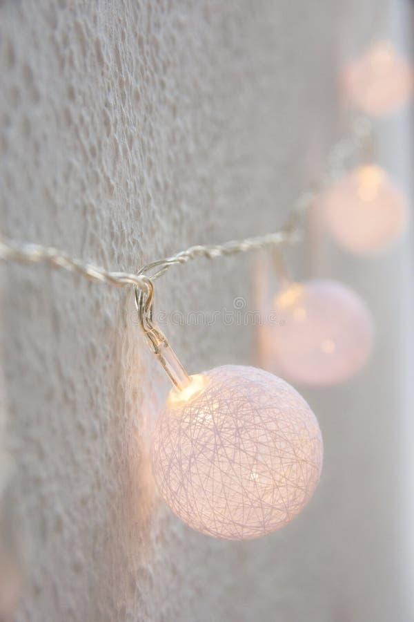 Priorità bassa di nuovo anno di natale Palle di cotone dorate pastelli d'attaccatura Garland White Wall Background Stile scandina fotografia stock libera da diritti
