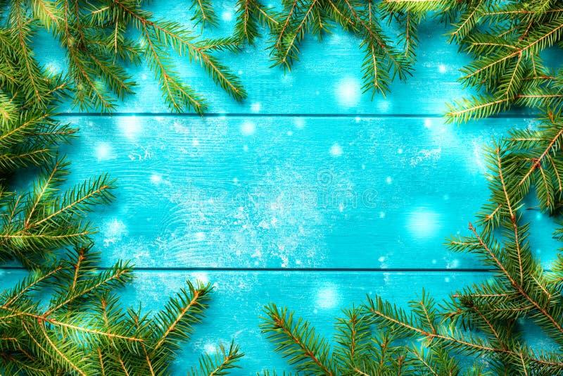 Priorit? bassa di natale Rami di albero dell'abete di Natale con neve sul bordo di legno rustico blu con lo spazio della copia fotografia stock