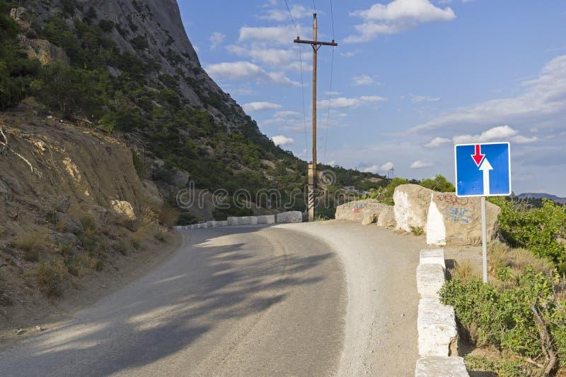 Prioritet för ` för trafiktecken över mötande trafik` på bergvägen arkivbilder