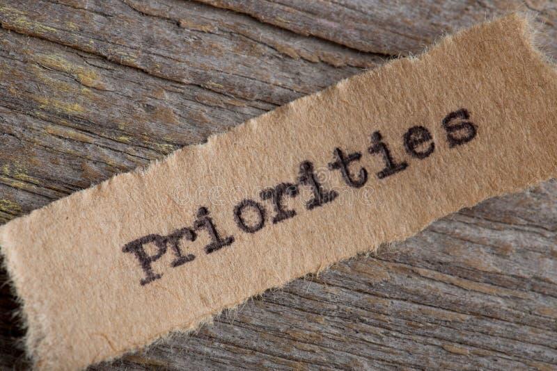 Prioriteter - ord på ett stycke av pappersslut upp, idérikt motivationbegrepp för affär royaltyfri bild
