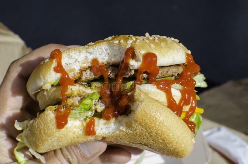 Pris un hamburger de morsure avec le ketchup de sauce tomate là-dessus photos stock