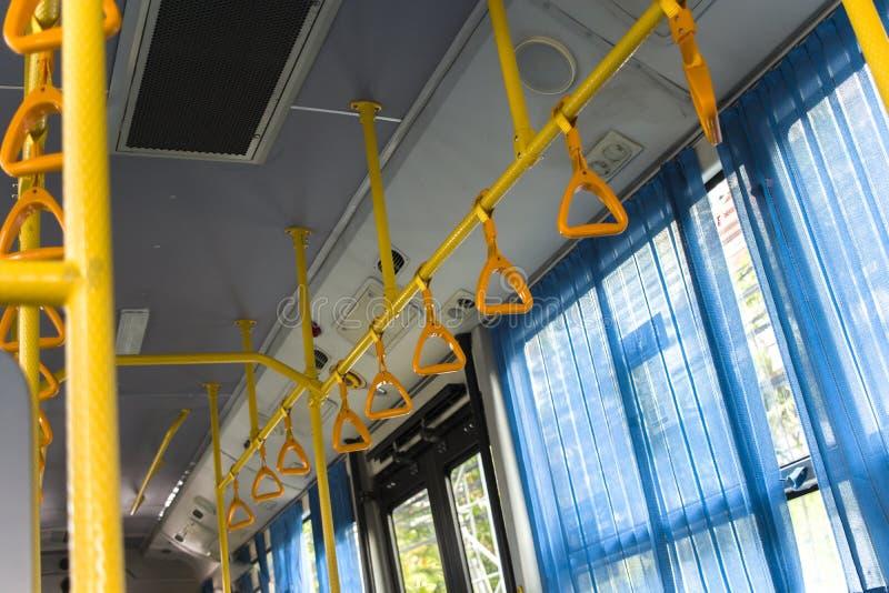 Prise accrochante jaune pour des passagers de position dans un autobus moderne Transport suburbain et urbain photo stock