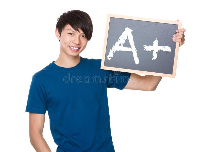 Prise asiatique d'homme avec le tableau noir et A de représentation plus la marque image libre de droits