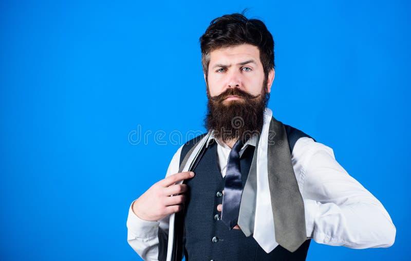 Prise barbue de hippie d'homme peu de cravates sur le fond bleu Type avec la barbe choisissant la cravate Le guide des messieurs  photos stock