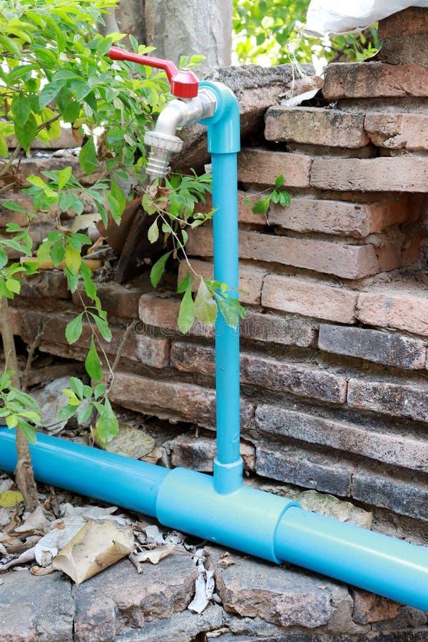 Prise d'eau Robinet bleu de tube et la valve rouge de volet photographie stock