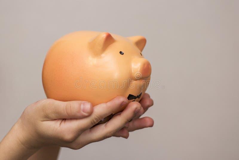 Prise d'enfant une banque de porc, un argent ?conomisant pour le futur concept d'?ducation fille de c?t? jugeant peu porcin photos stock