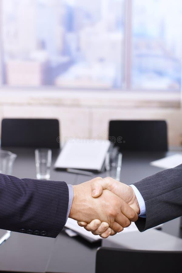 Prise de contact d'hommes d'affaires au-dessus de table photographie stock