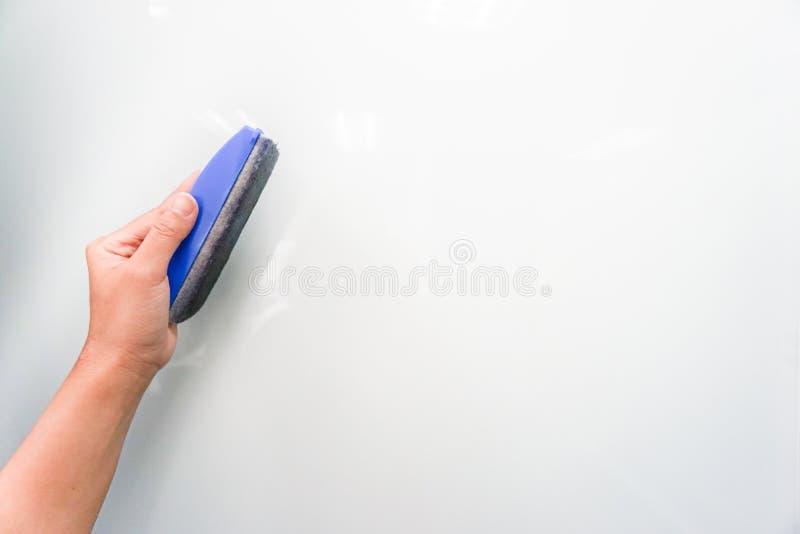 prise de femme essuyant la brosse sur le conseil blanc photos stock
