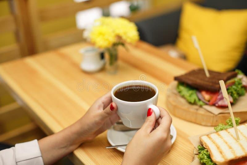 Prise de femme par tasse de café à la table en bois de backgroud, sur laquelle mensonges un sandwich images stock