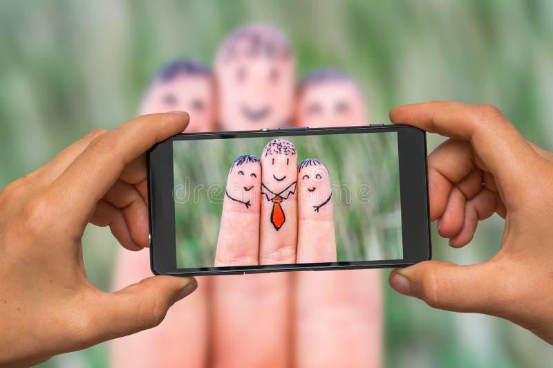 Prise de la photo des doigts heureux avec le téléphone portable images libres de droits