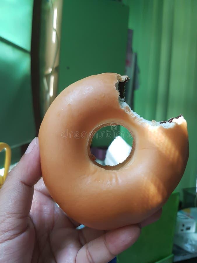 Prise de main du ` s d'homme un beignet bited de chocolat dans la chambre image libre de droits
