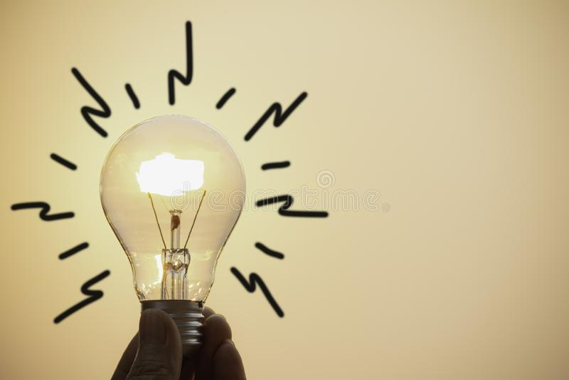 Prise de main une ampoule sur le fond de coucher du soleil pour l'énergie économisante et le concept créatif photographie stock