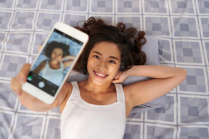 Prise de Selfie dans le lit photographie stock libre de droits