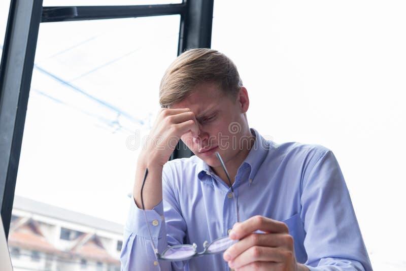 Prise fatiguée d'homme d'affaires des lunettes massag stressant de jeune homme photo stock