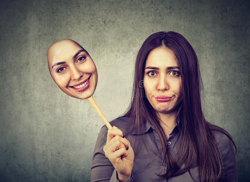 Prise mécontente contrariée grincheuse de femme d'un masque heureux photographie stock