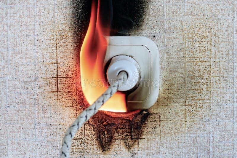 prise sur le feu il est vrai la fonte en plastique se produit prise insérée A oublié d'arrêter le fer photo libre de droits