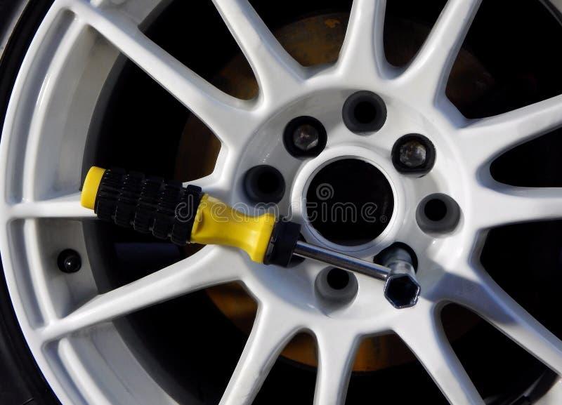 Prise tubulaire de vis à l'intérieur du modèle de crochet de la roue de voiture blanche photographie stock