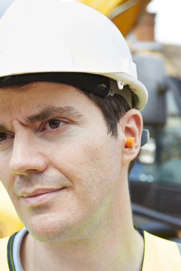 Prises de Wearing Protective Ear de travailleur de la construction photos stock