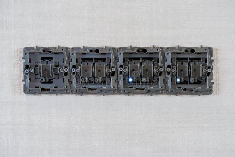 Prises ouvertes de courant électrique sur le fond, la réparation et le support blancs de mur Les pattes de LED sont allumées Pris photographie stock libre de droits