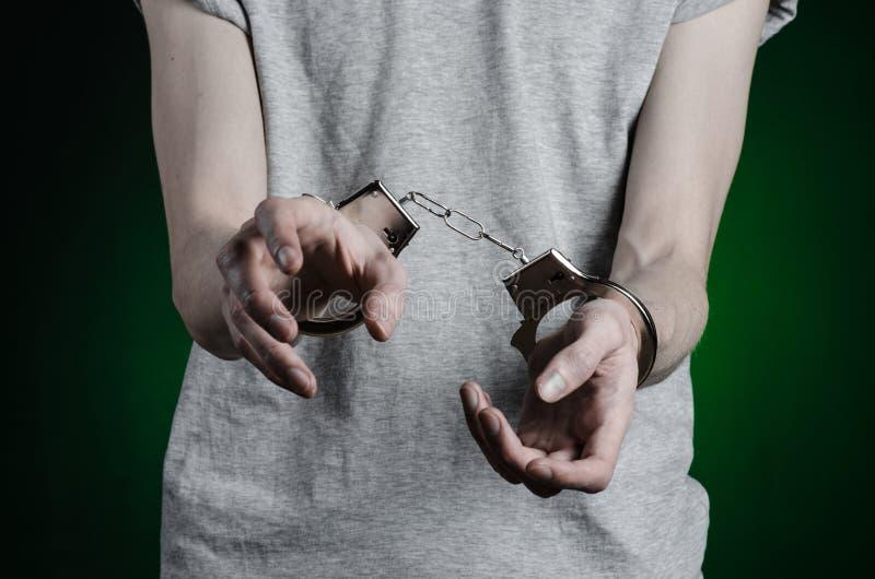 Prisión y tema condenado: hombre con las esposas en sus manos en una camiseta gris y tejanos en un fondo verde oscuro en el stu foto de archivo