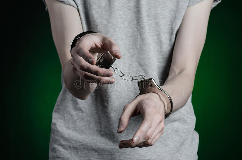 Prisión y tema condenado: hombre con las esposas en sus manos en una camiseta gris y tejanos en un fondo verde oscuro en el stu imagenes de archivo