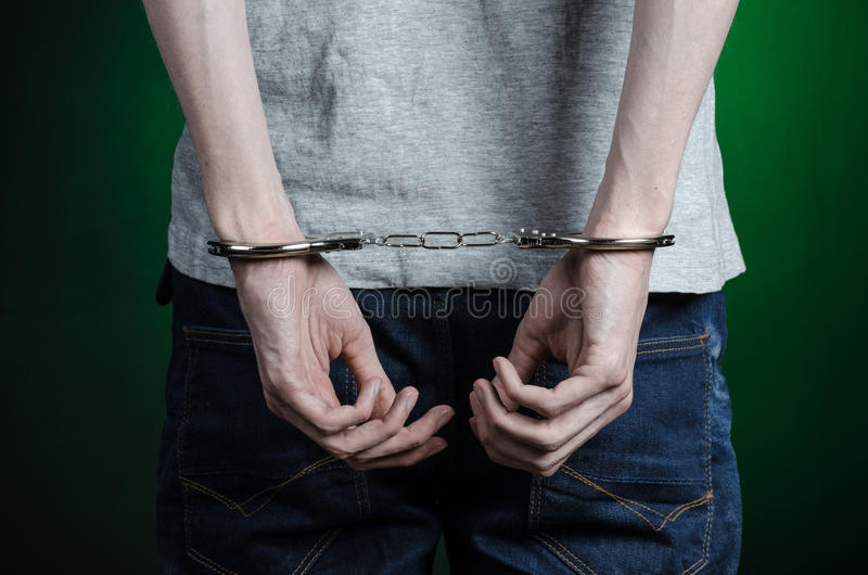 Prisión y tema condenado: hombre con las esposas en sus manos en una camiseta gris y tejanos en un fondo verde oscuro en el stu fotografía de archivo libre de regalías