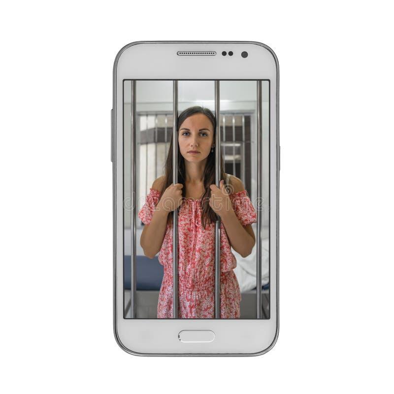 Prisioneiro da jovem mulher na cadeia do telefone celular Conceito da dependência em dispositivos móveis fotografia de stock royalty free