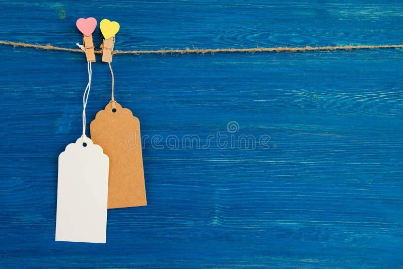 Prislapp- eller etikettuppsättningen för tomt papper och träbenet dekorerade på hjärtor som hänger på ett rep på den blåa träbakg arkivbilder