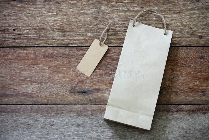 Prislapp- och pappersshoppingpåse på trä arkivbild