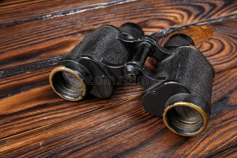 Prismáticos del primer en un fondo de madera marrón de la tabla imagen de archivo libre de regalías